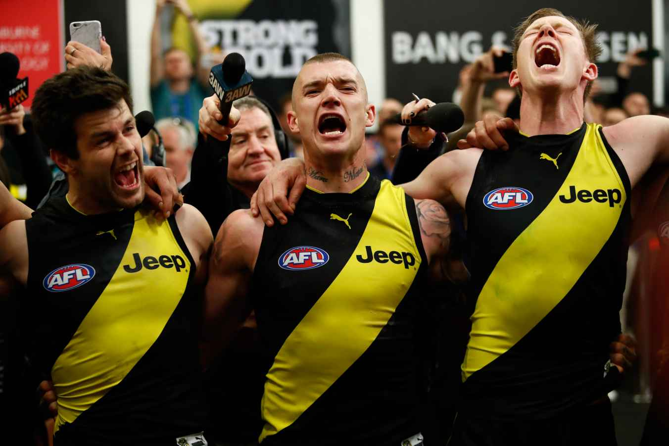 SEPTEMBER 23: (L-R) Trent Cotchin, Dustin Martin and Jack Riewoldt of the Tigers sing the team song during the 2017 AFL Second Preliminary Final match between the Richmond Tigers and the GWS Giants at the Melbourne Cricket Ground on September 23, 2017 in Melbourne, Australia. (Photo by Adam Trafford/AFL Media/Getty Images)