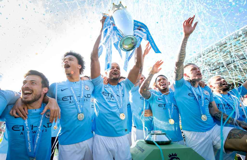 Vincent Kompany holds aloft the Premier League trophy after Manchester City defend their title